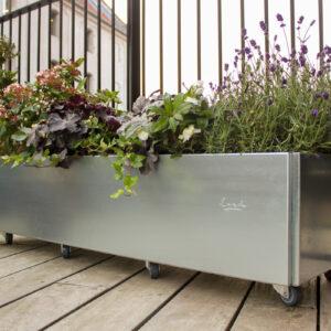 Land Classic 40x120 cm galvanisert plantekasse med hjul fra LandHage.no på stor balkong