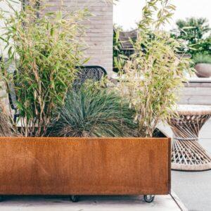 Land Classic 40x120 cm mobil plantekasse i rust fra LandHage.no med bambus på terrassen